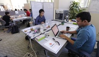 In this Thursday, June 30, 2016 photo, Babson College graduate school alumnus Abhinav Sureka, of Mumbai, India, right, types in his work space at the college in Wellesley, Mass. Some U.S. colleges are starting programs to help their alumni get visas through what critics say is a legal loophole. Foreign grads who want to stay and start a business typically apply for one of the 85,000 H-1B visas that the U.S. gives out each year. But college employees are exempt from that cap, so schools like UMass, Babson and CUNY have launched programs to hire alumni and foreign entrepreneurs and help them grow their businesses here. (AP Photo/Charles Krupa)