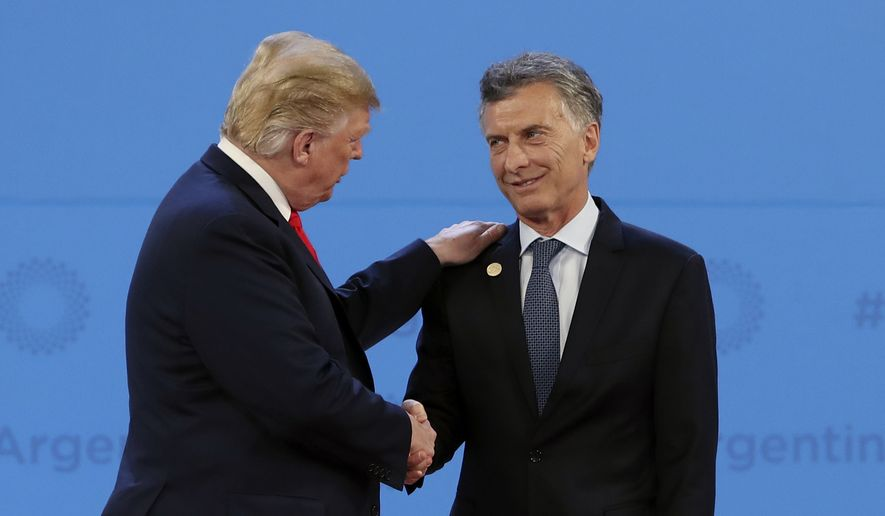 Argentina's President Mauricio Macri, right, welcomes President Donald Trump to the start of the G20 Leader's Summit at the Costa Salguero Center in Buenos Aires, Argentina, Friday, Nov. 30, 2018. (AP Photo/Ricardo Mazalan)