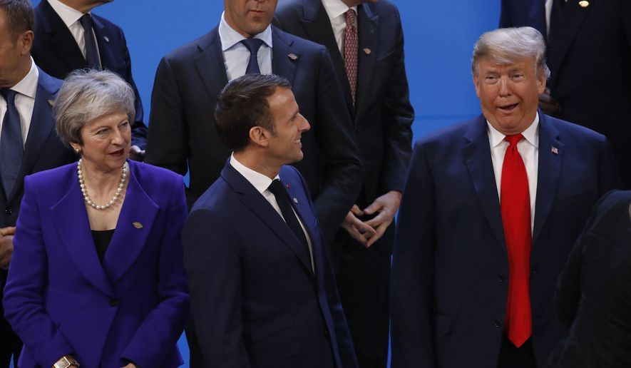 Britain's Prime Minister Theresa May, France's President Emmanuel Macron, center, and President Donald Trump gather for the group photo during the Group of 20 summit at the Costa Salguero Center in Buenos Aires, Argentina, Friday, Nov. 30, 2018. (Andres Martinez Casares/Reuters Pool Photo via AP)