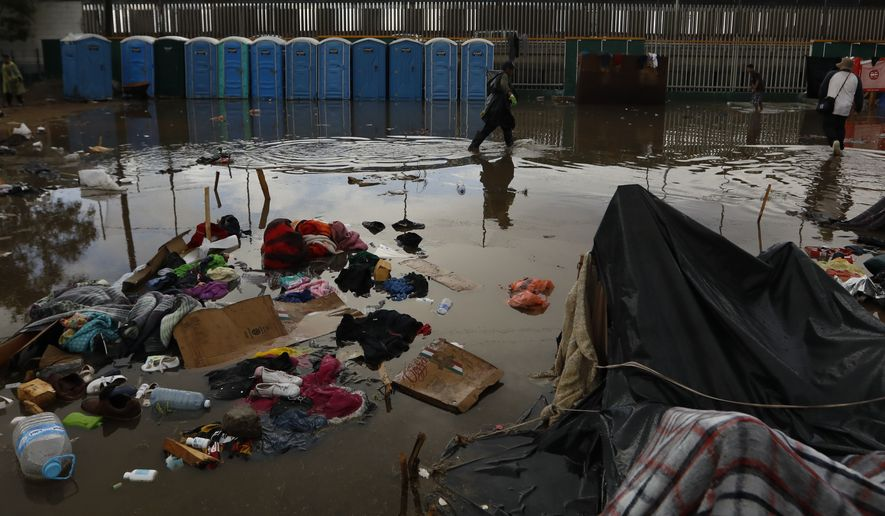 A man walks past flooded belongings, between bouts of heavy rain at a sports complex sheltering thousands of Central Americans in Tijuana, Mexico, Thursday, Nov. 29, 2018. Aid workers and humanitarian organizations expressed concerns Thursday about the unsanitary conditions at the sports complex in Tijuana where more than 6,000 Central American migrants are packed into a space adequate for half that many people and where lice infestations and respiratory infections are rampant.(AP Photo/Rebecca Blackwell)