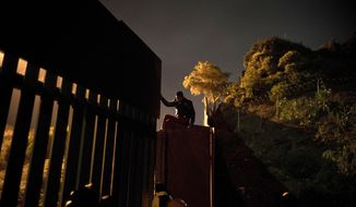 A Honduran migrant climbs the border wall separating Tijuana, Mexico and San Diego, before crossing to the U.S with his son in Tijuana, Mexico, Thursday, Nov. 29, 2018. Aid workers and humanitarian organizations expressed concerns Thursday about the unsanitary conditions at the sports complex in Tijuana where more than 6,000 Central American migrants are packed into a space adequate for half that many people and where lice infestations and respiratory infections are rampant. (AP Photo/Ramon Espinosa)