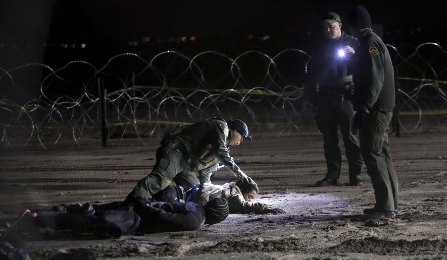 A U.S. Border Patrol agent pats down Honduran migrants after they crossed onto U.S territory from Tijuana, Mexico, Friday, Nov. 30, 2018. Thousands of migrants who traveled via a caravan members want to seek asylum in the U.S. but may have to wait months because the U.S. government only processes about 100 of those cases a day at the San Ysidro border crossing in San Diego. (AP Photo/Felix Marquez)