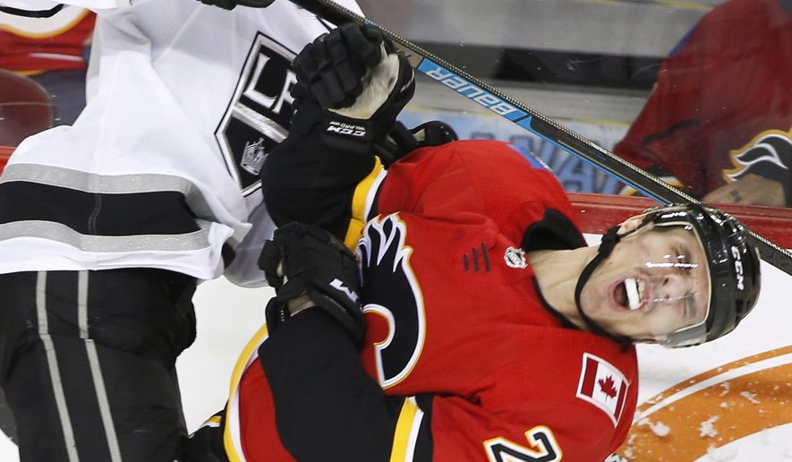 Los Angeles Kings center Adrian Kempe (9) hits Calgary Flames right wing Garnet Hathaway (21) and picks up a penalty during second-period NHL hockey game action in Calgary, Alberta, Friday., Nov. 30, 2018. (Larry MacDougal/The Canadian Press via AP)