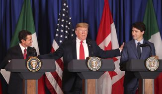 President Donald Trump, center, reaches out to Mexico's President Enrique Pena Nieto, left, and Canada's Prime Minister Justin Trudeau as they prepare to sign a new United States-Mexico-Canada Agreement that is replacing the NAFTA trade deal, during a ceremony at a hotel before the start of the G20 summit in Buenos Aires, Argentina, Friday, Nov. 30, 2018. The USMCA, as Trump refers to it, must still be approved by lawmakers in all three countries. (AP Photo/Martin Mejia) **FILE**