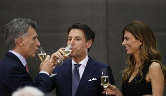 Argentina's President Mauricio Macri, left, and Argentina's first lady Juliana Awada, right, share a glass of champagne with Italy's Prime Minister Giuseppe Conte at the presidential palace in Buenos Aires, Argentina, Thursday, Nov. 29, 2018. Leaders from the Group of 20 industrialized nations will meet in Buenos Aires for two days starting Friday. (AP Photo/Natacha Pisarenko)