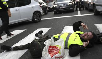 A demonstrator, called the yellow jackets, lays in a pedestrian crosswalk as he protests against rising fuel prices in Brussels, Friday, Nov. 30, 2018 (AP Photo/Francisco Seco)
