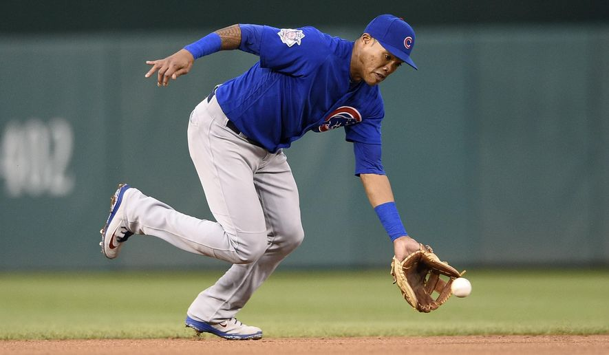 FILE - In this Sept. 8, 2018, file photo, Chicago Cubs shortstop Addison Russell fields a ground ball by Washington Nationals' Anthony Rendon during the fifth inning of the first baseball game of a doubleheader in Washington. The Cubs have offered suspended shortstop Russell a 2019 contract while maintaining his future with the team is not uncertain. Russell is serving a 40-game domestic violence suspension following allegations by his ex-wife. (AP Photo/Nick Wass, File)