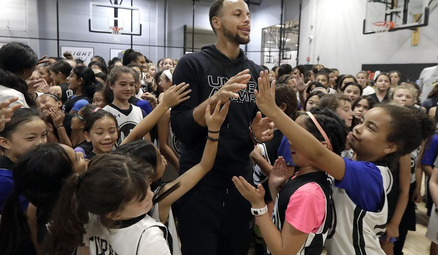 FILE - In this Aug. 14, 2018, file photo, Golden State Warriors' Stephen Curry, center, greets basketball camp participants after taking a group photo at Ultimate Fieldhouse in Walnut Creek, Calif. A letter from a 9-year-old girl has helped Stephen Curry fix online access to his shoes for kids. Riley Morrison of Napa, California, wrote to Curry to tell him she couldn't buy his Curry 5 shoes because they weren't available on the Under Armour website. They were only marketed to boys. (AP Photo/Jeff Chiu, File)