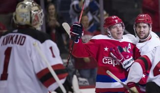 New Jersey Devils goaltender Keith Kinkaid (1) watches as Washington Capitals center Nicklas Backstrom (19), from Sweden, and right wing Tom Wilson (43) celebrate a goal by Backstrom during the first period of an NHL hockey game, Friday, Nov. 30, 2018, in Washington. (AP Photo/Alex Brandon)