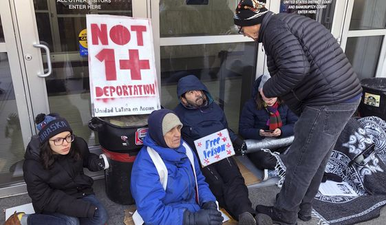 Supporters of Nelson Pinos, facing deportation, block the front doors of the federal building, Friday, Nov. 30, 2018, in Hartford, Conn. They are demanding that Immigration and Customs Enforcement allow Pinos, of Ecuador, to go home to his family in time for the holidays. He was ordered to leave the U.S. a few weeks before Christmas 2017. He instead sought sanctuary in a New Haven church. (AP Photo/Dave Collins)