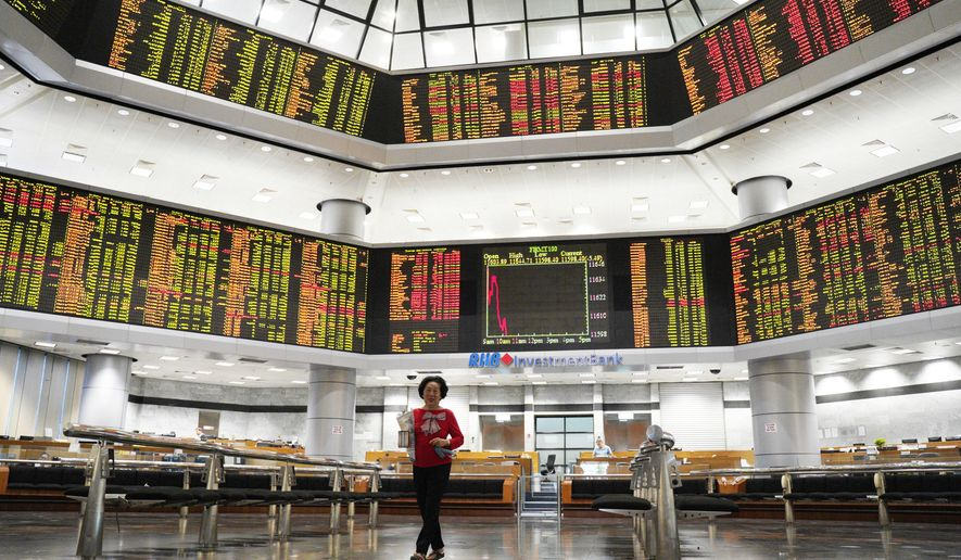 An Investor walks in front of stock trading boards at a private stock market gallery in Kuala Lumpur, Malaysia, Friday, Nov. 30, 2018. Share prices were mixed Friday in Asia ahead of the planned meeting by Presidents Donald Trump of the U.S. and Xi Jinping of China at the Group of 20 summit this weekend. (AP Photo/Yam G-Jun)