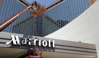 FILE - In this Tuesday, April 30, 2013, file photo, a man works on a new Marriott sign in front of the former Peabody Hotel in Little Rock, Ark.  Marriott says the information of up to 500 million guests at its Starwood hotels has been compromised. It said Friday, Nov. 30, 2018,  that there was a breach of its database in September, but also found out through an investigation that there has been unauthorized access to the Starwood network since 2014.(AP Photo/Danny Johnston, File)