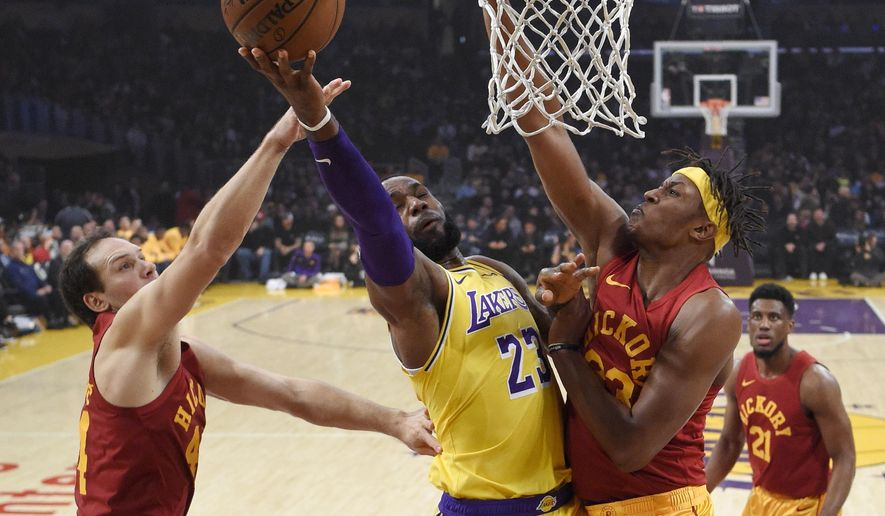 Los Angeles Lakers forward LeBron James, center, shoots as Indiana Pacers forward Bojan Bogdanovic, left, of Croatia, and center Myles Turner defend during the first half of an NBA basketball game Thursday, Nov. 29, 2018, in Los Angeles. (AP Photo/Mark J. Terrill)