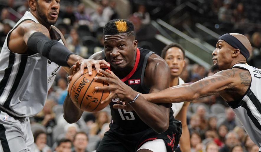 Houston Rockets' Clint Capela (15) drives between San Antonio Spurs' LaMarcus Aldridge, left, and Dante Cunningham during the first half of an NBA basketball game Friday, Nov. 30, 2018, in San Antonio. (AP Photo/Darren Abate)