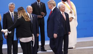 President Donald Trump arrives and joins other heads of state for a family photo at the G20 summit, Friday, Nov. 30, 2018 in Buenos Aires, Argentina.  From left in the front row are Singapore Prime Minister Lee Hsien Loong, Russian President Vladimir Putin and Brazil President Michel Temer.  From left on the top row are Rwanda President Paul Kagame and Saudi Arabia's crown Mohammed bin Salman. (AP Photo/Pablo Martinez Monsivais)