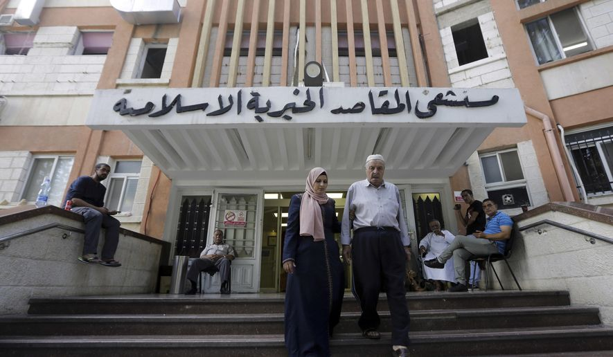 FILE - In this Sept. 9, 2018, file photo, Palestinians leave the Makassed hospital in east Jerusalem. US has cut funding to the six Jerusalem hospitals, including Makaseed, that provide care for Palestinians from the Israeli-occupied West Bank and the Gaza Strip. For two years, the Trump administration has unabashedly slashed U.S. aid to the Palestinians. Now, amid signs it may finally roll out its long-awaited Middle East peace plan, the administration is scrambling to save what little remaining Palestinian assistance it provides.(AP Photo/Mahmoud Illean, File)