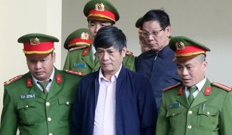 Former police generals Nguyen Thanh Hoa, center front row, and Phan Van Vinh, right second row, are escorted by police to a courtroom of People's Court in northern province of Phu Tho, Vietnam, Friday, Nov. 30, 2018. The court jailed the two former police generals for protecting a multimillion-dollar online gambling ring as the Communist government steps up its crackdown on graft. Former national police chief Phan and former head of hi-tech crimes police department Nguyen were sentenced to nine and 10 years respectively after being convicted of abuse of power at the end of the three-week trial. (Nguyen Trung Kien/Vietnam News Agency via AP)