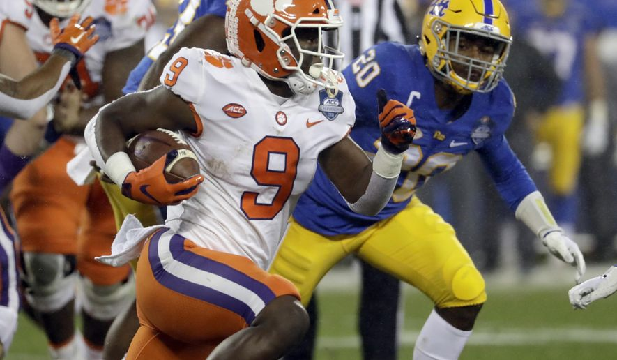 Clemson's Travis Etienne (9) runs past Pittsburgh's Dennis Briggs (20) in the first half of the Atlantic Coast Conference championship NCAA college football game in Charlotte, N.C., Saturday, Dec. 1, 2018. (AP Photo/Chuck Burton)