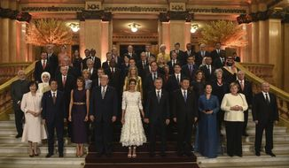 In this photo released by the press office of the G20 Summit, leaders and their partners pose for a group photo prior to a gala dinner at the Colon Theater in Buenos Aires, Argentina, Friday, Nov. 30, 2018. Leaders from the Group of 20 industrialized nations are meeting in Buenos Aires for two days starting today. (G20 Press Office via AP)
