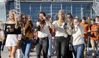 Texas fans head to a tailgate party before the Big 12 Conference championship NCAA college football game against Oklahoma on Saturday, Dec. 1, 2018, in Arlington, Texas. (AP Photo/Jeffrey McWhorter)