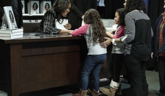 """Former First Lady Michelle Obama meets two young girls during an appearance for her book, """"Becoming,"""" in New York, Friday, Nov. 30, 2018. Combined hardcover, e-book and audio sales in the U.S. and Canada topped 2 million copies in the first 15 days, Crown Publishing announced Friday. (AP Photo/Richard Drew)"""