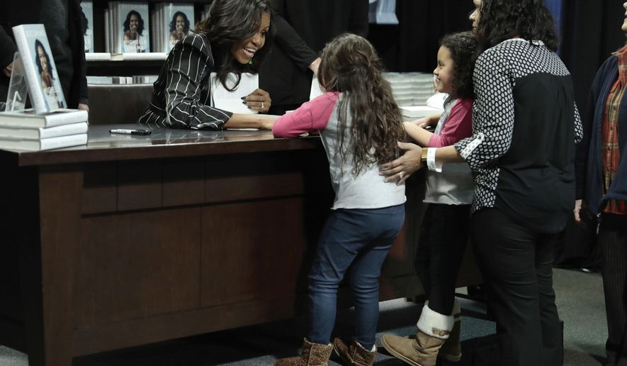 "Former First Lady Michelle Obama meets two young girls during an appearance for her book, ""Becoming,"" in New York, Friday, Nov. 30, 2018. Combined hardcover, e-book and audio sales in the U.S. and Canada topped 2 million copies in the first 15 days, Crown Publishing announced Friday. (AP Photo/Richard Drew)"