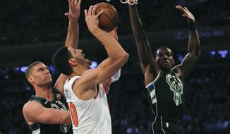 New York Knicks center Enes Kanter (00) puts up a shot against Milwaukee Bucks center Brook Lopez, left, during the first quarter of an NBA basketball game, Saturday, Dec. 1, 2018, in New York.(AP Photo/Julie Jacobson)