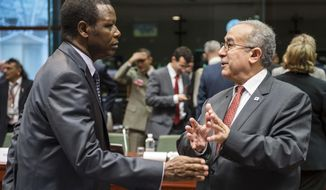 FILE - In this Tuesday, Feb. 5, 2013 file photo, African Union Commissioner for Peace and Security Ramtane Lamamra, right, talks with United Nations High Representative for Mali Pierre Buyoya during a ministerial meeting of the support and follow-up group on the situation in Mali, at the European Council building in Brussels, Belgium. Burundi's attorney general late Friday, Nov. 30, 2018 issued 17 international arrest warrants for people suspected of involvement in the assassination of the country's first democratically elected president, naming Pierre Buyoya, now the high representative of the African Union. (AP Photo/Geert Vanden Wijngaert, File)