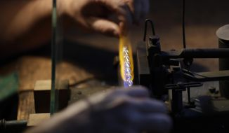 In this picture taken on Wednesday, Nov. 28, 2018, Marek Kulhavy blows small glass beads in the village of Ponikla, Czech Republic. A small family business in a mountainous village in northern Czech Republic is the last place where traditional Christmas decorations from blown glass beads are made. (AP Photo/Petr David Josek)