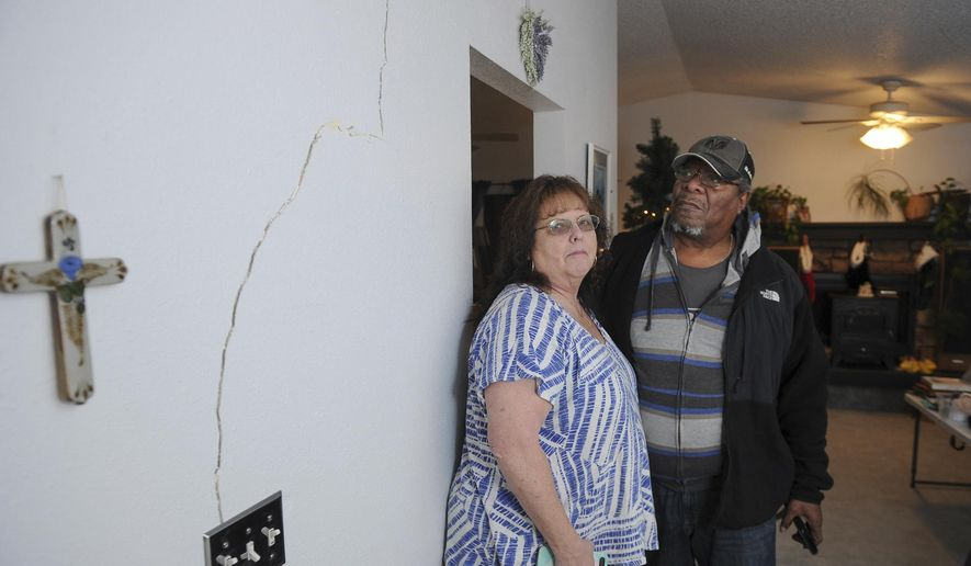 Al and Lyn Matthews show structural cracks in their home in south Anchorage, Alaska, following earthquakes Friday, Nov. 30, 2018. (AP Photo/Michael Dinneen)