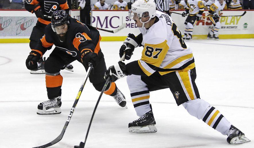 Sidney Crosby (87) has a shot deflected by Philadelphia Flyers' Radko Gudas (3) during the second period of an NHL hockey game in Pittsburgh, Saturday, Dec. 1, 2018. (AP Photo/Gene J. Puskar)