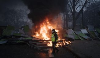 A demonstrator walks past a burning barricade near the Arc de Triomphe on the Champs-Elysees avenue during a demonstration Saturday, Dec.1, 2018 in Paris. A French protest against rising taxes and the high cost of living turned into a riot Saturday in Paris as police fired tear gas and water cannon in street battles with activists wearing the fluorescent yellow vests of a new movement. (AP Photo/Kamil Zihnioglu)