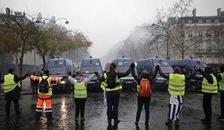 Demonstrators wearing yellow jackets make a chain in front of police forces near the Champs-Elysees avenue during a demonstration Saturday, Dec.1, 2018 in Paris. French authorities have deployed thousands of police on Paris' Champs-Elysees avenue to try to contain protests by people angry over rising taxes and Emmanuel Macron's presidency. (AP Photo/Kamil Zihnioglu)