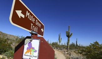 Signs direct hikers, cyclists and joggers along the Maricopa Trail inside the White Tank Mountain Regional Park Wednesday, Nov. 28, 2018, in Waddell, Ariz. Maricopa County has completed a 315-mile (507-kilometer) hiking and biking trail that circles Phoenix and most of its suburbs.  (AP Photo/Ross D. Franklin)