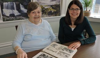 In this recent photo, former MASH 4077 nurse Helen Faso and her daughter, Aimee, look over a photo album in Wheeling, W.Va., Faso kept from her time in Korea. (Heather Ziegler/The Intelligencer via AP)