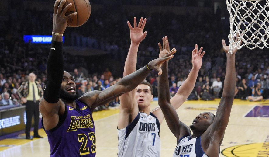 Los Angeles Lakers forward LeBron James, left, shoots as Dallas Mavericks forward Dwight Powell, center, and forward Dorian Finney-Smith defend during the first half of an NBA basketball game Friday, Nov. 30, 2018, in Los Angeles. (AP Photo/Mark J. Terrill)