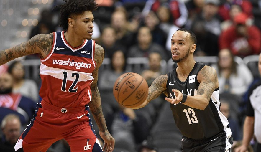 Brooklyn Nets guard Shabazz Napier (13) passes the ball past Washington Wizards forward Kelly Oubre Jr. (12) during the first half of an NBA basketball game Saturday, Dec. 1, 2018, in Washington. (AP Photo/Nick Wass)