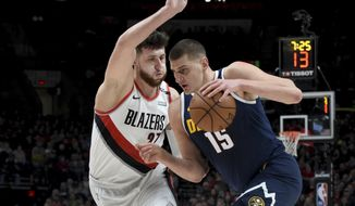 Denver Nuggets center Nikola Jokic, right, drives to the basket on Portland Trail Blazers center Jusuf Nurkic during the first half of an NBA basketball game in Portland, Ore., Friday, Nov. 30, 2018. (AP Photo/Steve Dykes)