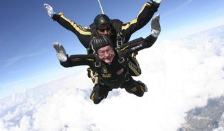 FILE - In this Nov. 10, 2007, file photo provided by the U.S. Army Golden Knights, former President George H.W. Bush free falls with Golden Knights parachute team member Sgt. 1st Class Mike Elliott, as he makes a dramatic entrance to his presidential museum during a rededication ceremony in College Station, Texas. Bush died at the age of 94 on Friday, Nov. 30, 2018, about eight months after the death of his wife, Barbara Bush. (Sgt. 1st Class Kevin McDaniel/U.S. Army via AP, File)