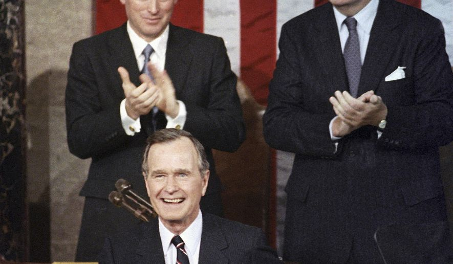 FILE - In this Jan. 31, 1990, file photo, President George H.W. Bush receives applause from Vice President Dan Quayle, left, and House Speaker Thomas Foley prior to delivering his first State of the Union address on Capitol Hill in Washington. Bush died at the age of 94 on Friday, Nov. 30, 2018, about eight months after the death of his wife, Barbara Bush. (AP Photo/Bob Daugherty, File)