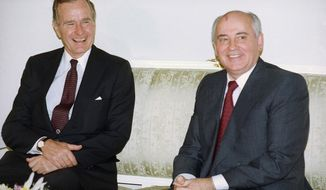 """In this file photo taken on Tuesday, Oct. 29, 1991, U.S. President George H. Bush, left, and Soviet President Mikhail Gorbachev sit together at the Soviet Embassy after meeting in Madrid, Spain. Former Soviet premier Mikhail Gorbachev expressed his """"deep condolences"""" Saturday Dec. 1, 2018, to the family of former U.S President George Bush and all Americans following his death, aged 94. (AP Photo/Liu Heung Shing, File)"""