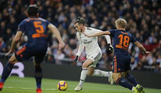 Real Madrid's Gareth Bale, centre, tries to get a cross in during a Spanish La Liga soccer match between Real Madrid and Valencia at the Santiago Bernabeu stadium in Madrid, Spain, Saturday, Dec. 1, 2018. (AP Photo/Paul White)