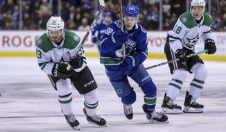 Dallas Stars' Joel Hanley (39) vies for control of the puck against Vancouver Canucks' Adam Gaudette (88) during second period NHL hockey action in Vancouver on Saturday, Dec. 1, 2018. (Ben Nelms/The Canadian Press via AP)