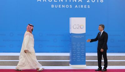 Saudi Arabia's Crown Prince Mohammed bin Salman, left, enters to shake hands with Argentina's President Mauricio Macri at the start of the G20 summit in Buenos Aires, Argentina, Friday, Nov. 30, 2018. Leaders from the Group of 20 industrialized nations are meeting in Buenos Aires for two days starting today. (AP Photo/Ricardo Mazalan)