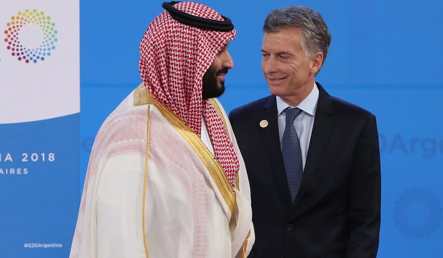 Saudi Arabia's Crown Prince Mohammed bin Salman (left) walks away after shaking hands with Argentina's President Mauricio Macri at the Group of 20 summit in Buenos Aires on Friday. The death of a journalist has made other leaders wary of the prince. (ASSOCIATED PRESS)