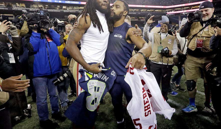 Seattle Seahawks wide receiver Doug Baldwin, right, hugs San Francisco 49ers cornerback Richard Sherman, left, after they traded jerseys following an NFL football game, Sunday, Dec. 2, 2018, in Seattle. The Seahawks won 43-16. (AP Photo/Elaine Thompson)