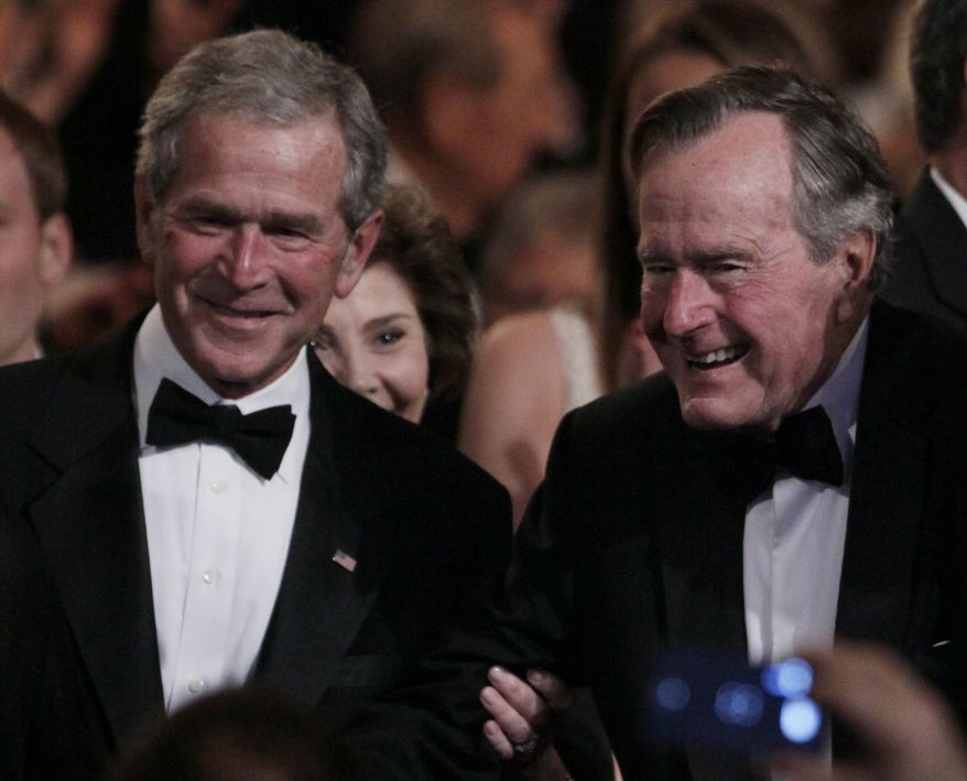 "Former President George H. W. Bush, right, is helped by his son former President George W. Bush, left, to his seat at the Kennedy Center, Monday, March 21, 2011, before the ""All Together Now - A Celebration of Service"" performance in honor of former President George H. W. Bush.  (AP Photo/Carolyn Kaster)"