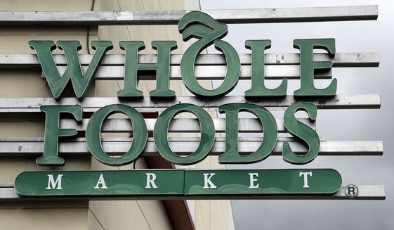 A sign at a Whole Foods Market greets shoppers, Monday, Aug. 28, 2017, in Tampa, Fla. Parent company Amazon has announced they will drop the prices on certain food items at the stores. (AP Photo/Chris O'Meara)