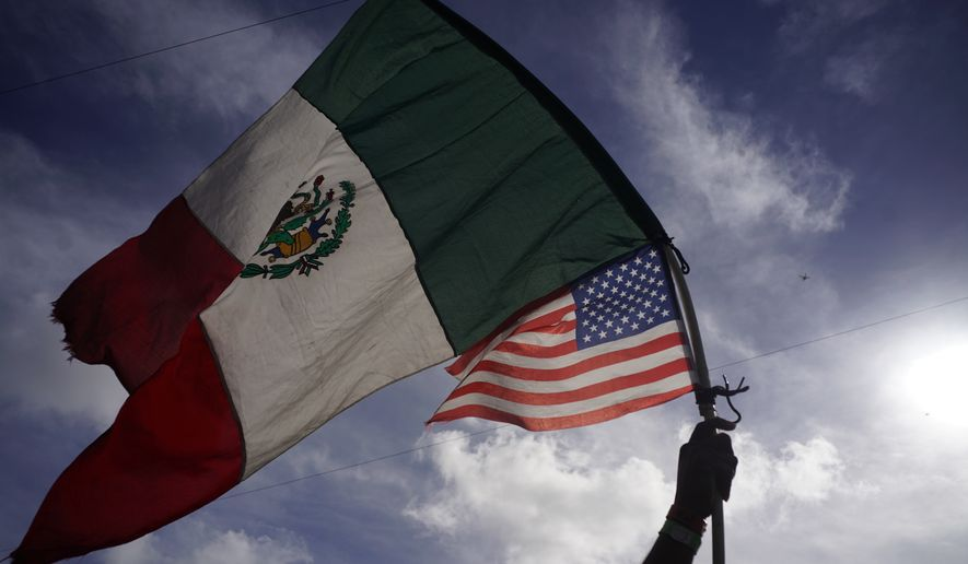A Honduran migrant holds up Mexican and U.S. flags as he joins a small group of migrants trying to cross the border together at the Chaparral border crossing in Tijuana, Mexico, Thursday, Nov. 22, 2018. A small group of Central American migrants marched peacefully to the border crossing in Tijuana Thursday to demand better conditions and push to enter the U.S. (AP Photo/Ramon Espinosa)