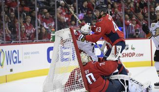 Anaheim Ducks left wing Andrew Cogliano, center, collides into the net after he scored a goal against Washington Capitals goaltender Braden Holtby, left, and right wing Tom Wilson, right, during second first period of an NHL hockey game, Sunday, Dec. 2, 2018, in Washington. (AP Photo/Nick Wass)